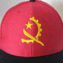 Casquette rouge, visière noire, logo brodé jaune, ambassade Angola